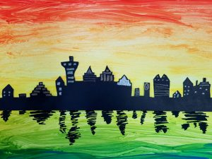 Cityscape with a painted sunset in the background, reflected water in the foreground and silhouetted buildings. Made by children in after school club.